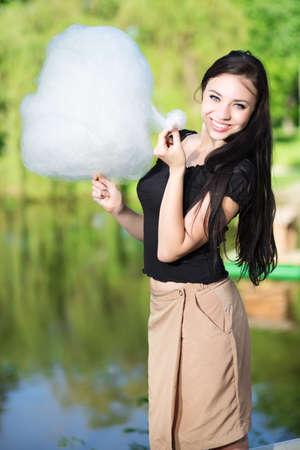 algodon de azucar: Mujer bonita sonriente posando con un caramelo de algodón cerca de la laguna