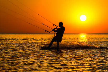 Silhouette of a kitesurfer sailing in the evening  Stock Photo