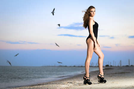 Young leggy curly woman on high platforms posing at sunset
