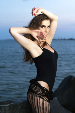 Elegant sexy young woman wearing black posing near the sea