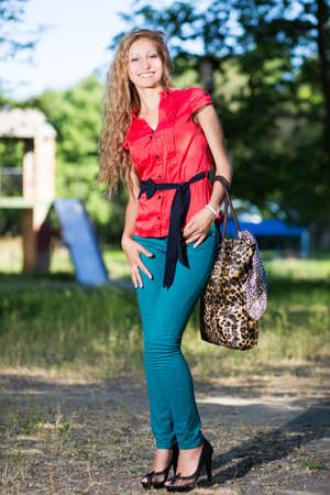 Cheerful young lady posing in blue jeans and red blouse photo