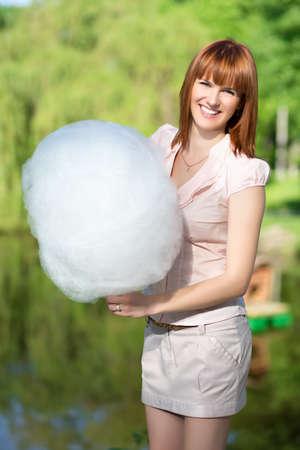algodon de azucar: Mujer pelirroja sonriente que desgasta la falda corta y la celebración de un algodón de azúcar