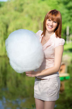 cotton candy: Smiling red-haired woman wearing short skirt and holding a cotton candy Stock Photo