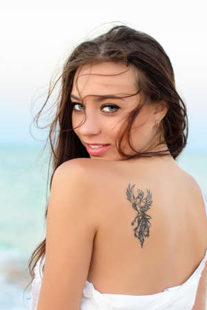 Portrait of sexy young brunette with tattoo