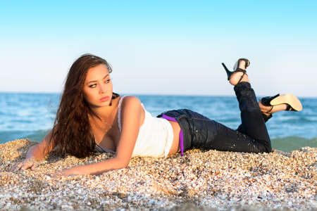 wet: Pretty thoughtful brunette lying on the beach Stock Photo