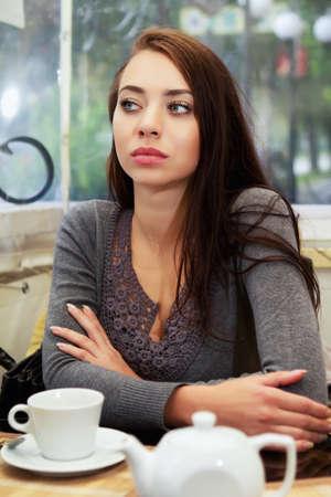 joyless: Pretty joyless woman waiting somebody in a cafe