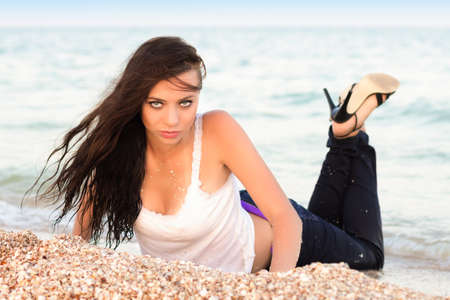 Provocative brunette in wet clothes posing on the beach photo