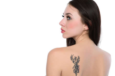 Sexy young naked brunette showing her tattoo. Isolated on white  photo