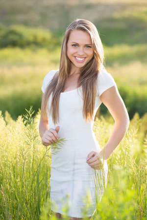 Cheerful young blonde wearing white dress posing on the meadow photo
