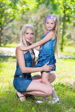 little girl posing: Pretty blond woman with nice little girl posing in the park