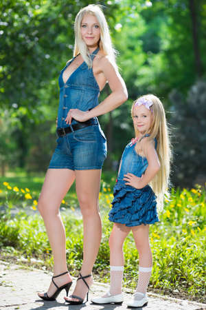 Pretty blond woman and little girl posing in jeans dresses