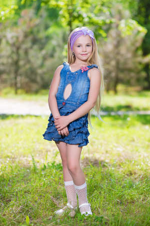 Beautiful little girl wearing jeans dress posing outdoors photo