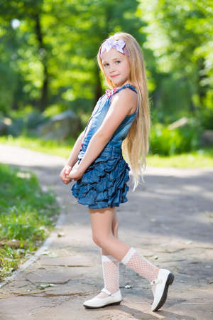 Adorable blond girl posing in jeans dress outdoors photo