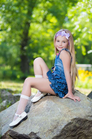 Pretty little girl in jeans dress sitting on the stone