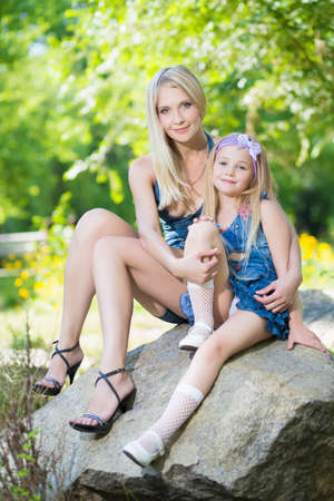 Pretty blond woman and her daughter sitting on the stone Stock Photo