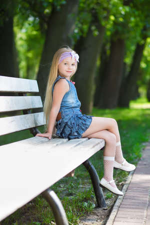Blond little girl sitting on the white bench Stock Photo