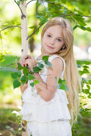 Portrait of nice little girl posing near the birch
