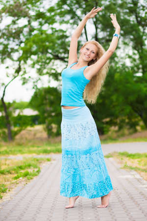 barefooted: Barefooted blond woman in long blue shirt and t-shirt posing on the pavement path