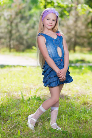 Little blond girl posing in jeans dress outdoors
