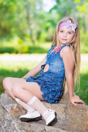 Little girl in blue jeans dress sitting on the stone
