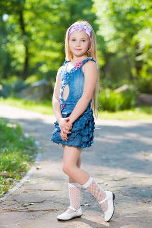 Una bonita y pequeña chica rubia en vaqueros alineada que presenta al aire libre