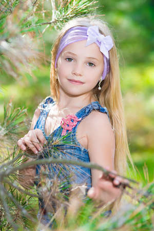 Portrait of blond girl posing in pine branches photo