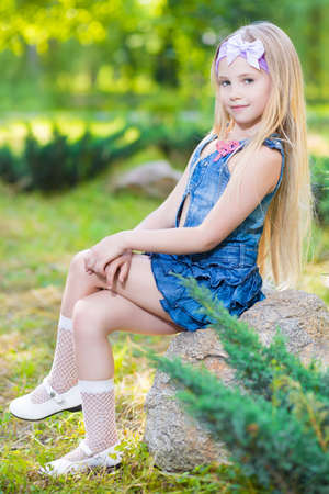 Beautiful little girl sitting on the stone outdoors photo
