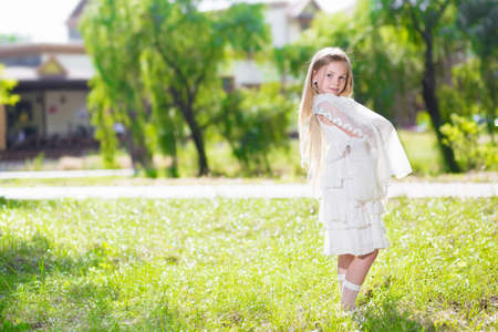 Cute little girl in white dress posing outdoors photo