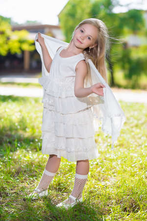Pretty little girl in white dress posing outdoors