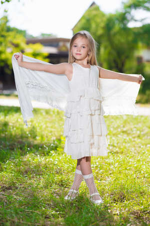 Beautiful little girl wearing white dress posing outdoors photo