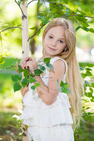 Portrait of nice little girl posing near the birch