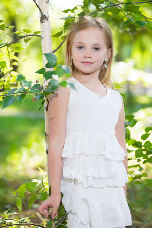 Portrait of beautiful blond girl posing near the birch in white dress photo