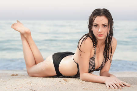 Sexy brunette in wet swimsuit posing near the sea photo