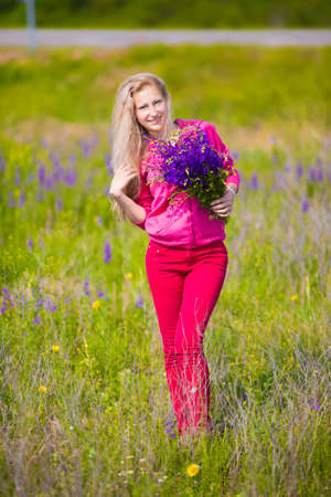 Pretty blond woman posing in the field with flowers photo