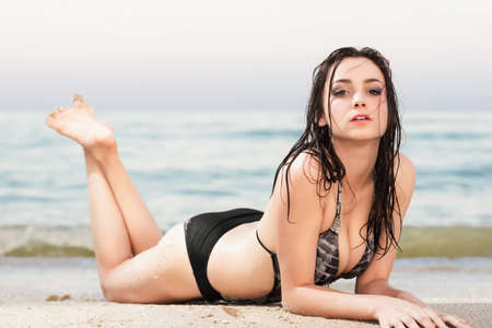 Pretty young woman posing in wet swimsuit near the sea photo