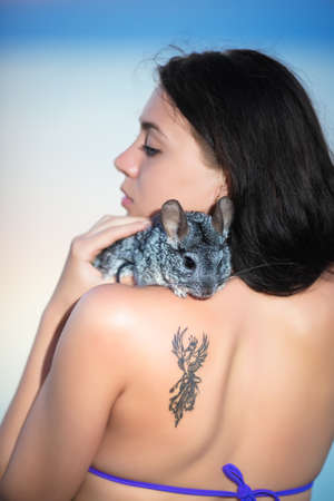chinchilla: Portrait of young brunette posing with chinchilla