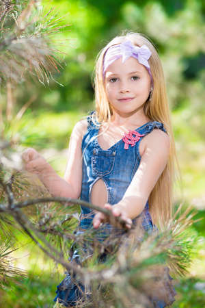 Portrait of pretty blond girl posing in pine branches photo