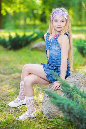 어린 소녀: 야외에서 돌에 포즈 좋은 작은 소녀