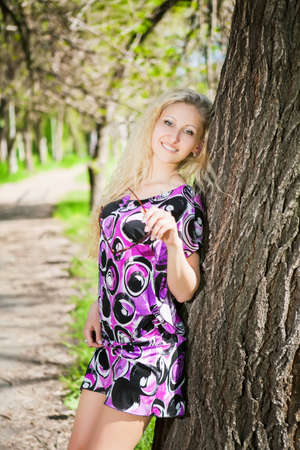Sexy blond woman posing in the park near a tree photo