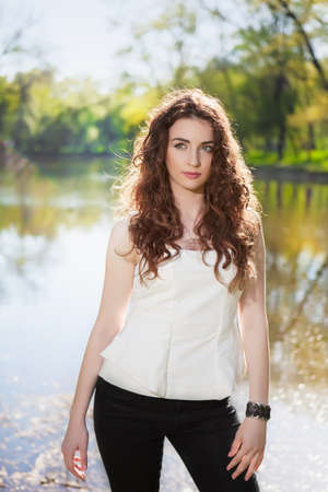 Pretty brunette posing in black pants and white blouse near the pond photo