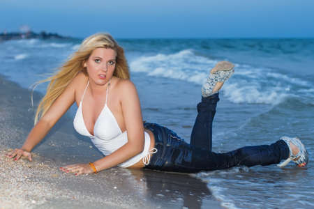 Attractive young caucasian woman posing on the beach photo