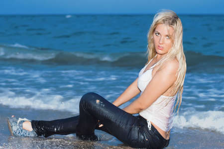 Stunning young blonde posing in wet clothes on the beach photo