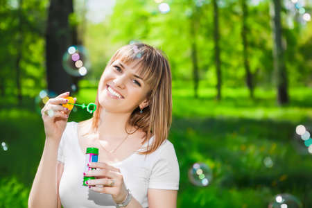 blowing bubbles: Portrait of cheerful young woman blowing bubbles in the park