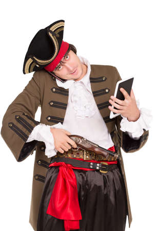 Young man in pirate costume posing with a tablet, mobile phone and pistol. Isolated on white photo