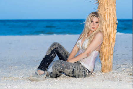 Stunning young blonde posing in wet clothes near a palm photo