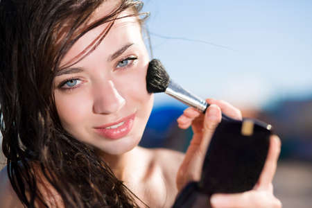 Portrait of pretty brunette posing with a brush for makeup