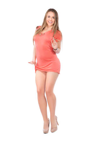 Smiling young blond woman posing in short pink dress. Isolated on white
