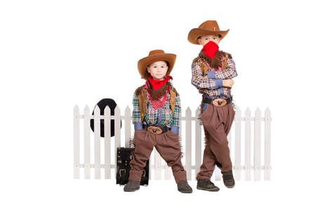 二人の少年がカウボーイの衣装を着ています。白で隔離されます。