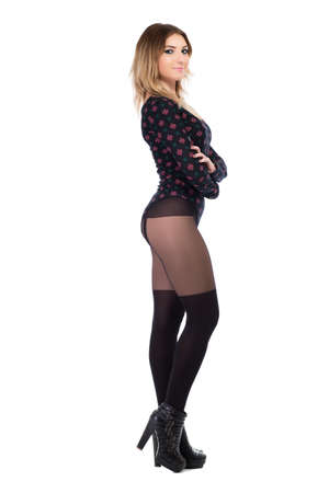 Pretty young woman posing in black tights and shoes. Isolated on white