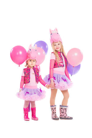 Two little girls posing in pink pony suit. Isolated on white photo
